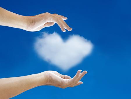 hand and heart cloud shape with blue sky photo