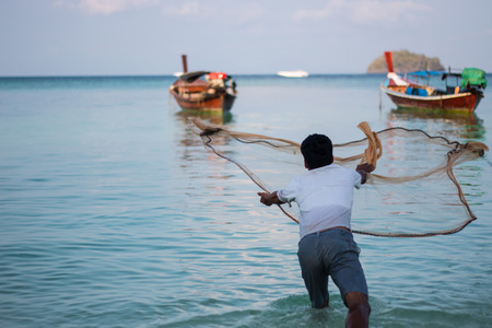 fish net: throwing fishing net on beach in Thailand Stock Photo