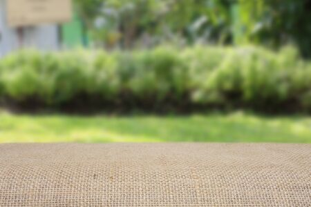picknick: empty table with sack and blur green nature bokeh background can be used for product display template
