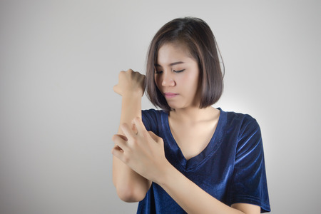Women scratch the itch with hand, arm Stock Photo
