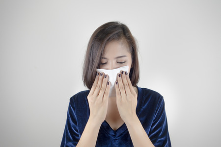 Woman having flu and holding a tissue