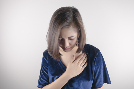 asian woman is clutching her chest. Heart disease. Acute pain possible heart attack. Healthcare, Medical and sickness concept Stok Fotoğraf - 82341263