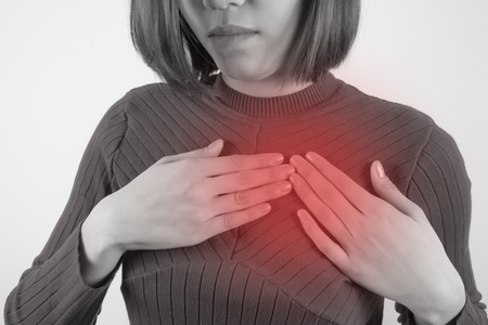 asian woman is clutching her chest. Heart disease. Acute pain possible heart attack. Healthcare, Medical and sickness concept