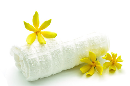Yellow fragrant flower, Ylang-Ylang flower (Cananga odroata) with towel in spa theme, isolated on a white background