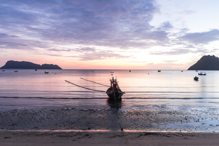 Beautiful sunrise over the sea with orange sky, mountains and fishing boats