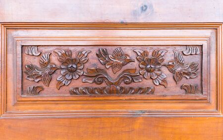 Details of a fine wood carving door, birds and flower