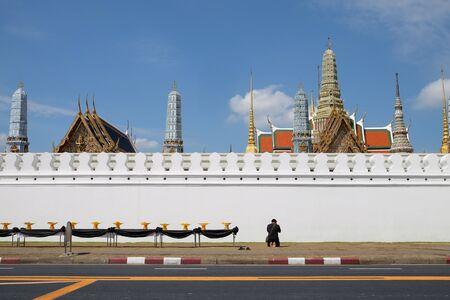 A man praying alone at outside of Grand Palace in Bangkok, Thailand