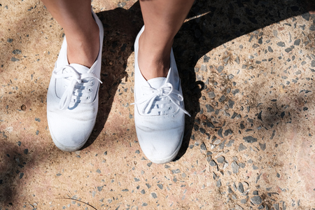g spot: White sneakers on girl legs on the street Stock Photo
