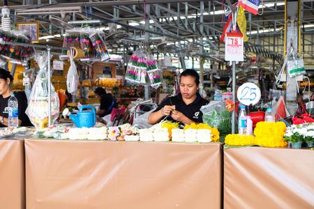 BANGKOK, THAILAND - October 23, 2017 : A woman string jasmine flowers garland at Pak Khlong Talat, the biggest flower market in Bangkok