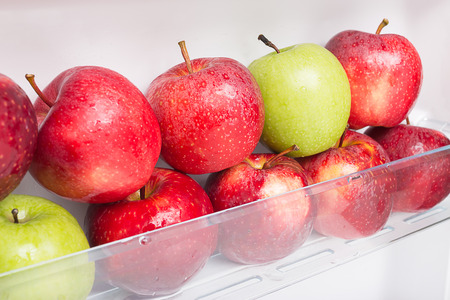 Fresh and clean apples on the refrigerator shelf. good to eat in diet.