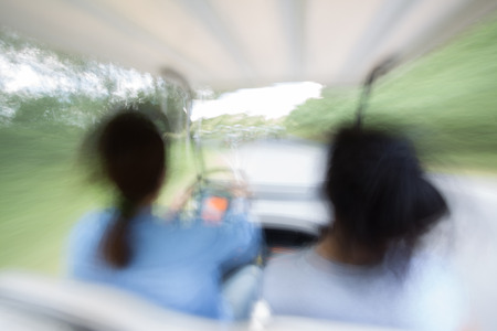 Mother and daughter Enjoy drivng golf car top speed in the blurred movement. photo