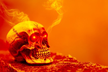 Abstract skull in orange tone with eye shining light and smoke. Concept