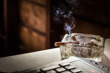 soustředění: Zátiší cigarety a sklo popelník. Někteří člověk, jako je kouření v pracovní doby pro make nápad.