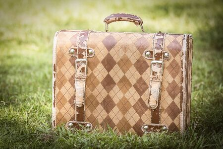 Old briefcase on grass  in vintage color.