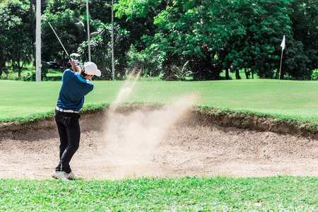 teen golf: Stop action yong asian golfer after explosion sand bunker.