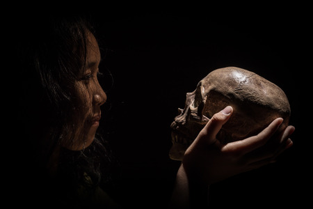 Yong girl gaze and holding mysterious skull in hand. in the low key tone. Stock Photo