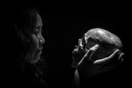 gaze: Yong girl gaze and holding mysterious skull in hand. in the low key and black and white tone. Stock Photo