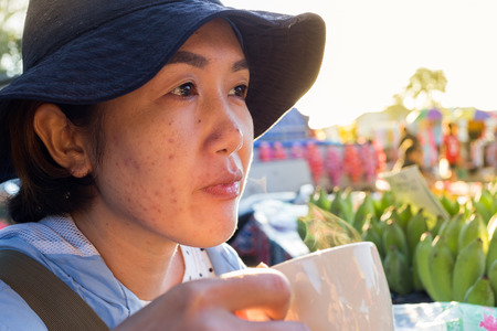 supplementary: Asian woman drinking supplementary food beverage facial acne and skin in the morning at  fresh food market.