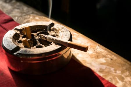 ashtray: Cigarette on stainless ashtray. on moring light.