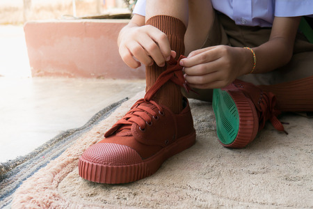 The student Leash shoelace new sneakers. Studen in new uniform try leash shoelace  new sneakers it a new experience first school start day.