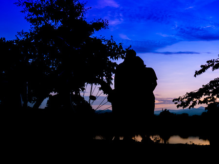 endearment: Silhouette man and woman endearment love romantic near river and sky in twilight time. Stock Photo