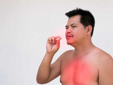 ratty: Adult asian man lighting up a cigarette. his face look old  shabby andGrey Hair by  toxic from cigarette.