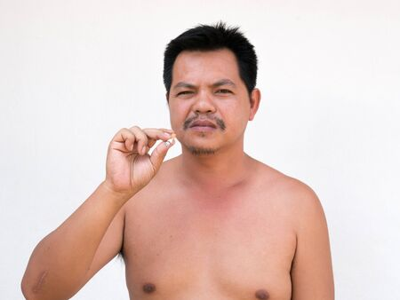 Adult asian man lighting up a cigarette. his face look old  shabby andGrey Hair by  toxic from cigarette.