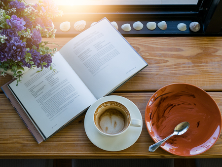 drinks after work: Empty coffee cup and empty plate after drink coffee and cake with book on wooden desk. Stock Photo