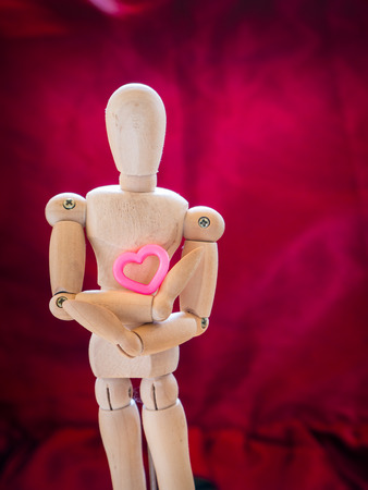 Still life wooden puppet and pink heart. concept everyting have love and heart. Stock Photo