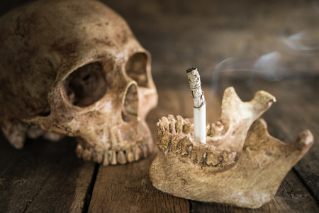 smoky black: Still life skull and cigarette burned with smoke on wood.