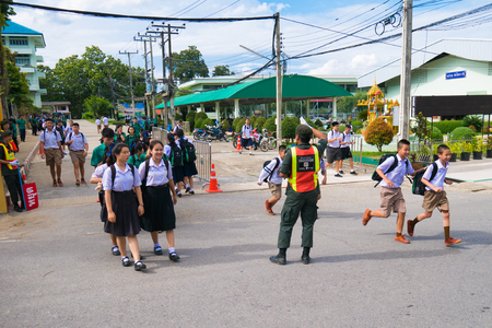 CHIANG RAI, THAILAND - MAY 21, 2017 : Asian student walk cross way safe by Reserve Officer Training Cops Student facilitate. 新聞圖片