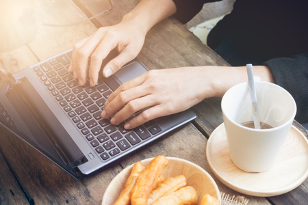 Hands woman on laptop keyboard and coffee with chinese bread stick.