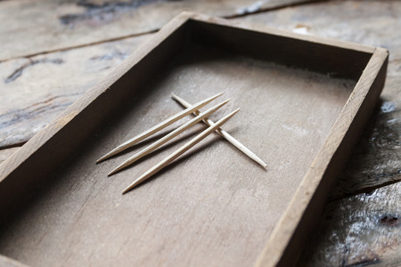 Bamboo  Toothpick on the wooden plate.  Toothpick is make for clean between the Teeth.