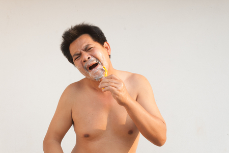 Asia man have Irritability and hurt from blunt blade razor with out cream foam. Stock Photo