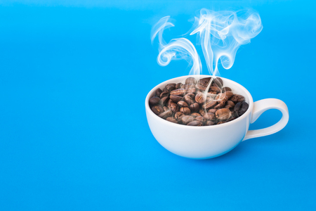 Coffee bean and with white cup hot and smoke on the blue background. 版權商用圖片