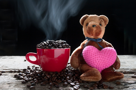 Coffee bean in the red cup with smoke and bear doll  Show heart like hot and fragrance smell from seed bean coffee.