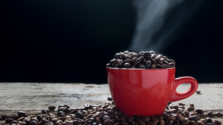 Coffee bean in the red cup with smoke. Show hot and fragrance smell from seed bean coffee. 版權商用圖片 - 100512559