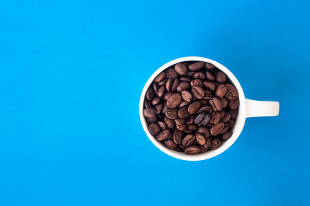 Coffee bean and with white cup on the blue background.