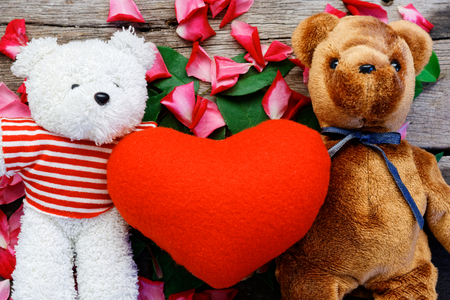 Two Toy bear doll have falling in love with Rose petals background in  valentine day. Foto de archivo - 122521324