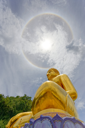 Big gold statue buddha under the corona ring sun light. 版權商用圖片 - 122540079