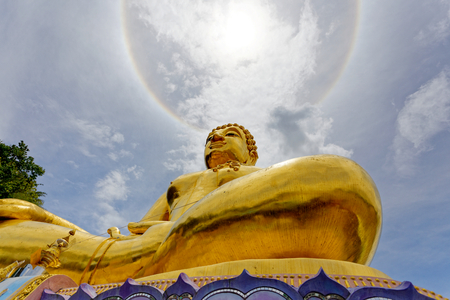 Big gold statue buddha under the corona ring sun light.