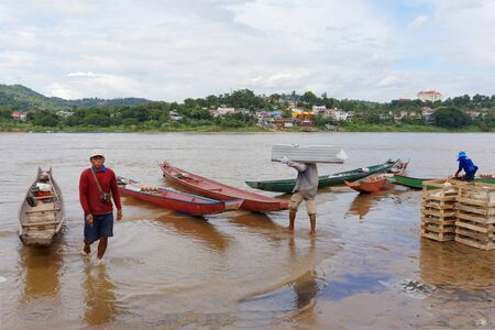 CHIANG RAI, THAILAND - JUNE 22, 2015: worker loading product to small boat  pass  Mekong River from thailand to border laos Country.