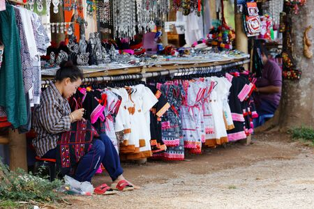 CHIANG RAI - APRIL 27 : Tribal woman Sewing traditional dress tribes near her shop on April 27, 2015 in Chiang Rai, Thailand.