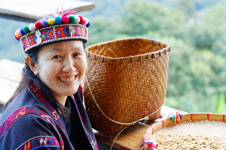 Asian woman in the tribe dress be smile happy with coffee seed