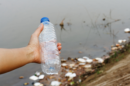 Hand holding empty bottle on Plastic garbage foam box in the river , pollution and environment in the water. 版權商用圖片 - 122520050
