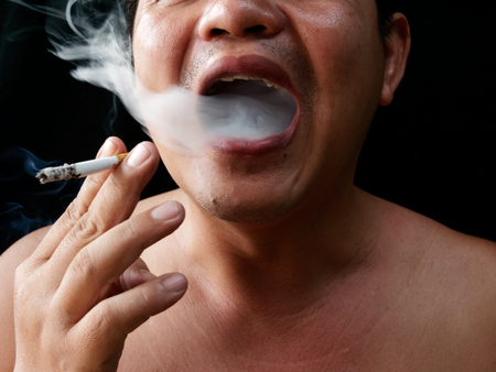 A man holding cigarette. Nicotine destroy teeth and gum healthy. it make effect Yellow stain, Tooth decay and Bad breath. world no tobacoo day. 版權商用圖片 - 126627865