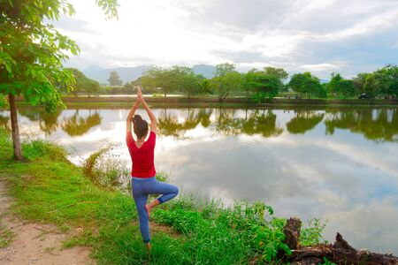 Girl try to learning tree pose yoga near peaceful nature  river and tree under warm light in the sunset.