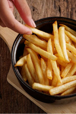 French fries with ketchup on a dark wood background. fastfood snack.