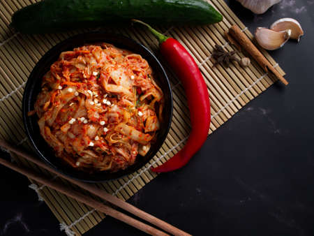Korean food, Cabbage kimchi in black dish set on dark background. Stockfoto