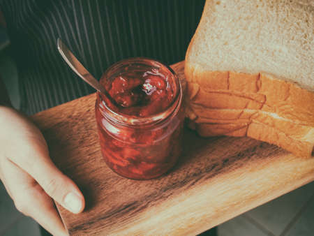 Red strawberry and peach yellow jam on plank wood and slice bread.